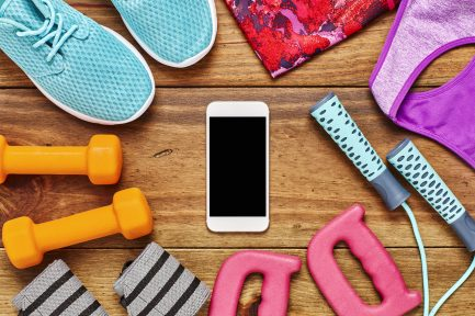 Directly above flat lay shot of mobile phone surrounded with exercise equipment on floor. Dumbbells are with jump rope  wristbands  shoes and clothing. The space on smart phone can be used for advertisement.